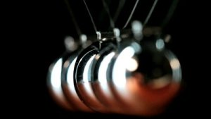 stock-footage-close-up-of-newton-s-cradle-desk-toy-pendulum-being-activated-black-background